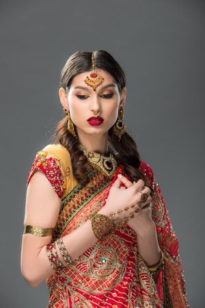 attractive indian woman in traditional clothing and accessories, isolated on grey