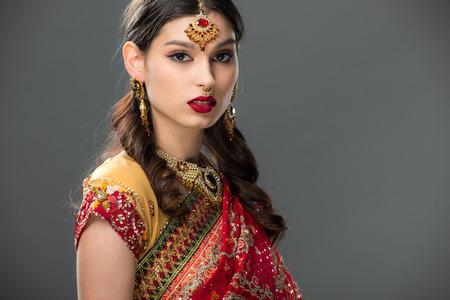 beautiful indian woman in sari and accessories, isolated on grey 版權商用圖片