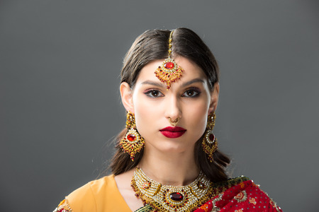 attractive indian woman in sari and accessories, isolated on grey Stock Photo - 117467264