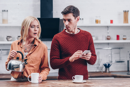 jealous young woman holding kettle and looking at husband with smartphone in kitchen