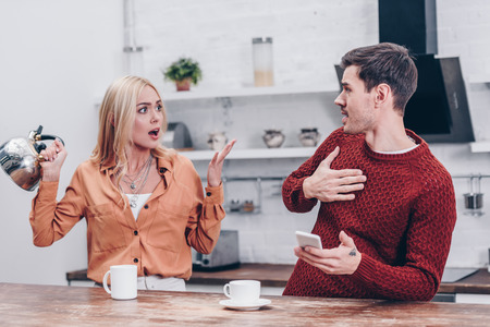 emotional young couple quarrelling in kitchen, mistrust concept Stock Photo