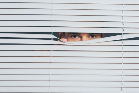 suspicious young man peeking and looking at camera through blinds, mistrust concept Stock Photo