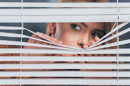Mujer joven mirando a otro lado y mirando a través de las persianas, concepto de desconfianza Foto de archivo
