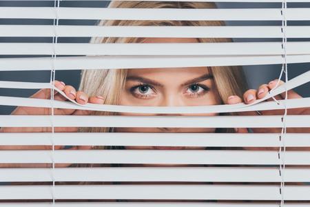 Mujer joven mirando a la cámara y mirando a través de las persianas Foto de archivo