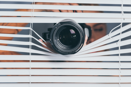 close-up view of camera and young woman spying through blinds Zdjęcie Seryjne