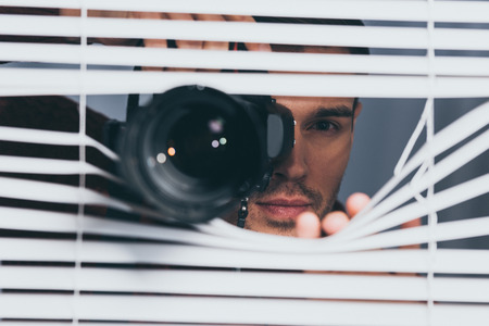 young man holding camera and looking at camera through blinds, mistrust concept