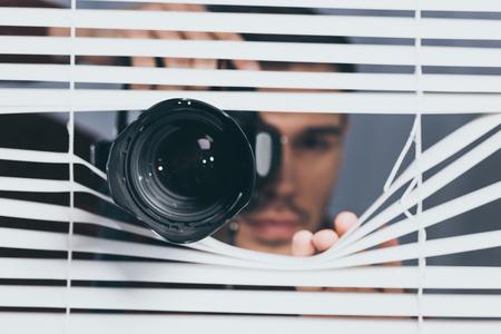 Nahaufnahme eines Mannes, der Kamera hält und durch Jalousien späht, Misstrauenskonzept