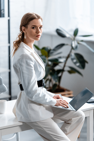 beautiful businesswoman in white formal wear sitting on desk, looking at camera and using laptop at workplace