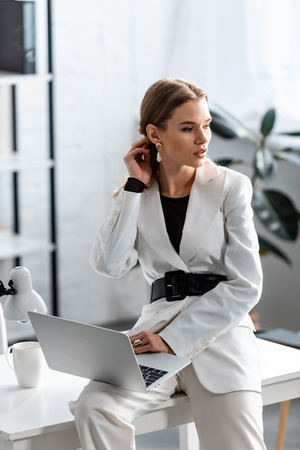 beautiful businesswoman in white formal wear sitting on desk with laptop and looking away