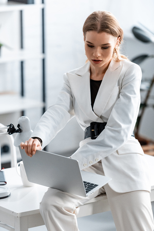 beautiful focused businesswoman in white formal wear sitting on desk and using laptop at workplace Imagens