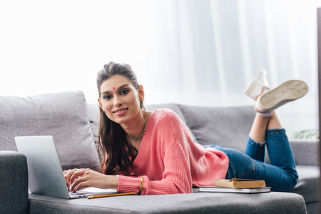 attractive indian woman with bindi studying with books and laptop on sofa Stock Photo