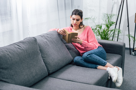 beautiful female indian student reading book on sofa