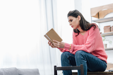 female indian student reading book at home