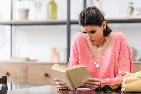 indian woman with bindi studying at home and reading book