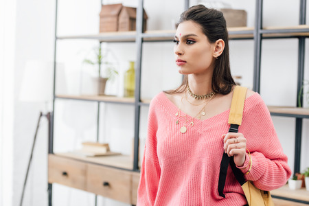 attractive indian woman in pink clothes with backpack at home