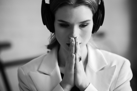 black and white portrait of beautiful woman in headphones with folded hands