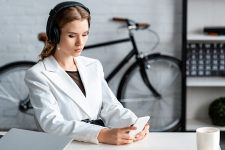 focused businesswoman in headphones sitting at desk and using smartphone at workplace Imagens