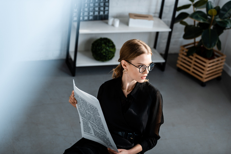 beautiful businesswoman in black clothes and glasses sitting at table and holding newspaper Imagens