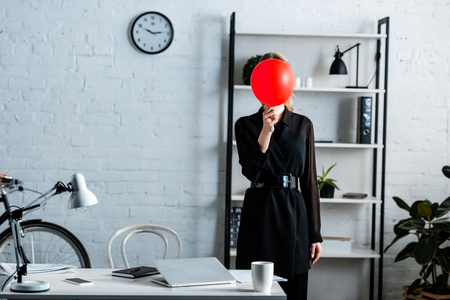businesswoman in black clothes standing near table and hiding face behind red balloon Imagens