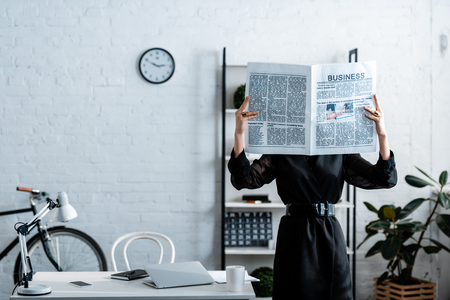 businesswoman in black clothes holding newspaper in front of face