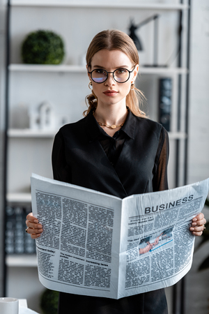 attractive businesswoman in black clothes and glasses holding newspaper and looking at camera