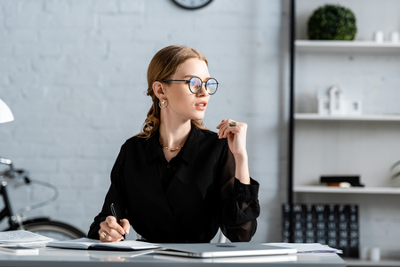 beautiful businesswoman in black clothes and glasses sitting on chair and whiting in note