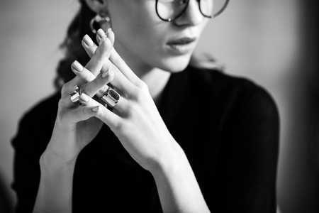 black and white of woman in black clothes and glasses touching rings 스톡 콘텐츠