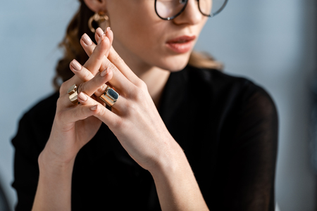 woman in black clothes and glasses touching rings