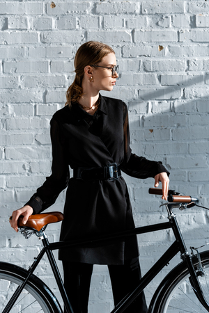cropped view of attractive woman in black clothes holding black bike with brown saddle Stock Photo