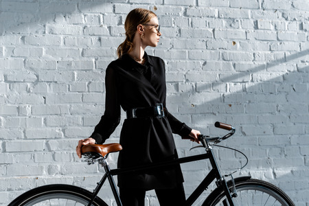 cropped view of attractive woman in black clothes holding multicolored bike