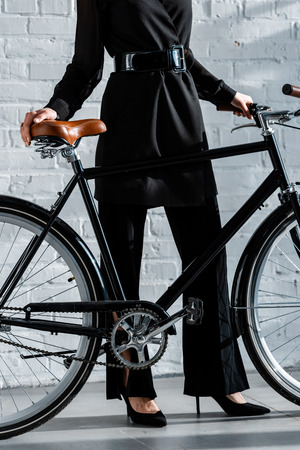 woman in black clothes holding black bike