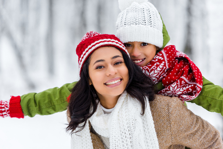 beautiful african american woman piggybacking cheerful daughter and looking at camera in winter park