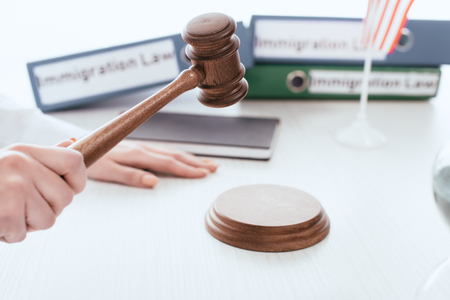 selective focus of gavel in hand of female judge with folders on background