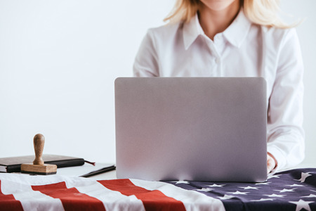 cropped view of woman using laptop near american flag isolated on white Imagens