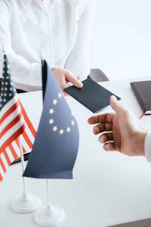 cropped view of female travel agent giving passport to tourist near american and european flags isolated on white