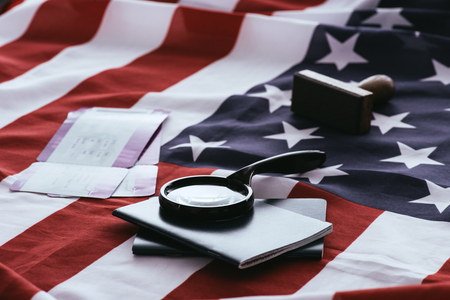 selective focus of passports and magnifier near tickets and american flag 스톡 콘텐츠