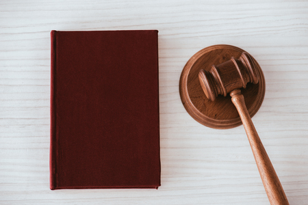 top view of wooden gavel near notebook on wooden table