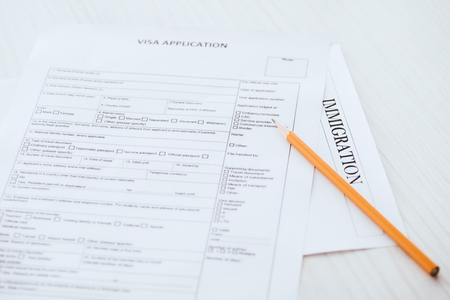 selective focus of  wooden pencil near document with visa application and immigration lettering
