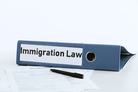 selective focus of folder with immigration law lettering near documents and pen Stock fotó