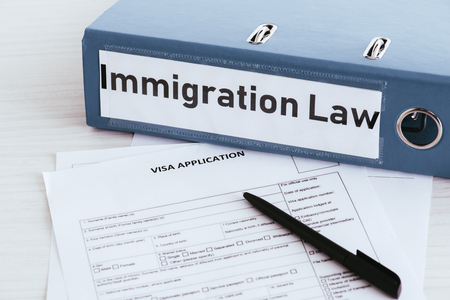 selective focus of folder with immigration law lettering near documents Foto de archivo - 117466591