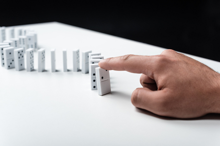 partial view of man pointing at domino row on white table isolated on black