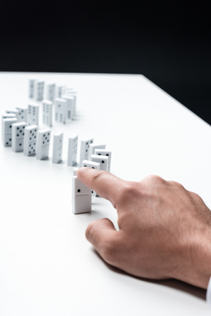 partial view of man pointing at domino row on white table