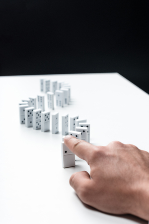 cropped view of man pointing at domino row on white table isolated on black