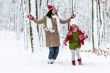beautiful african american woman and cute preteen daughter having fun in winter park