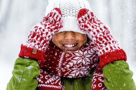 cute african american child with knitted hat pulled over eyes smiling during snowfall 스톡 콘텐츠