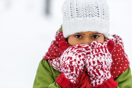 close up view of african american child in knitted hat, mittens and scarf looking at camera in winter