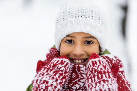 close up view of african american child in knitted hat, mittens and scarf smiling and looking at camera in winter