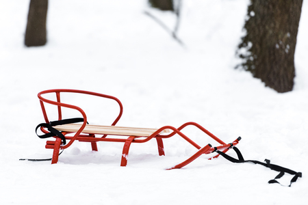red metal sledge on snow with trees at background in winter