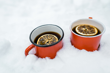 red cups of tea with lemon staying on snow Stock Photo