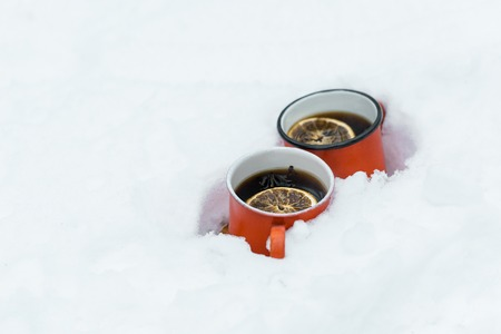 two red cups of tea with lemons slice standing in snowy forest